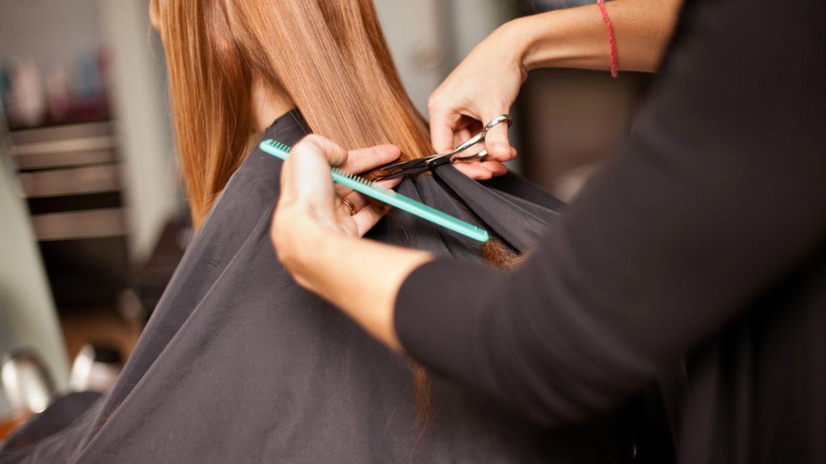 cabeleireira a cortar com tesoura e pente cabelo de mulher ruiva no salão de estética