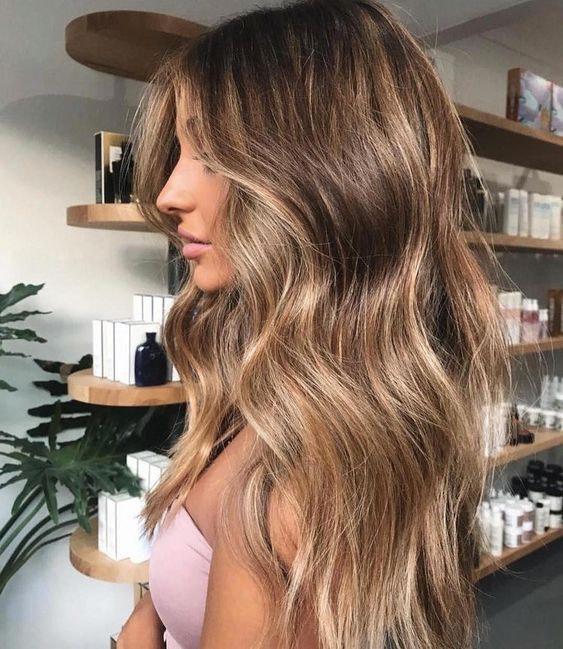 perfil de mulher com cabelo comprido castanho e madeixas loiras em loja de cosmética