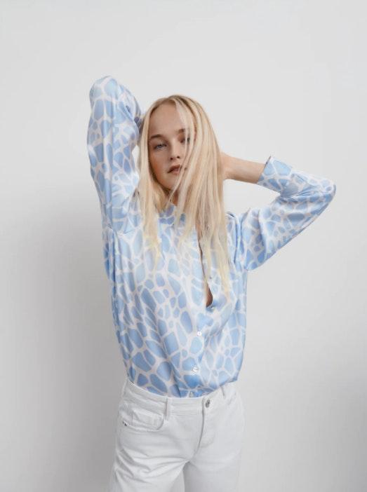 mulher loira de cabelo comprido e vestida com blusa azul da Zara e calças da Zara