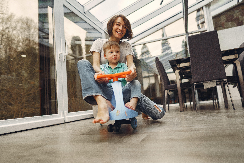 mãe e filho a brincar com um triciclo dentro de casa