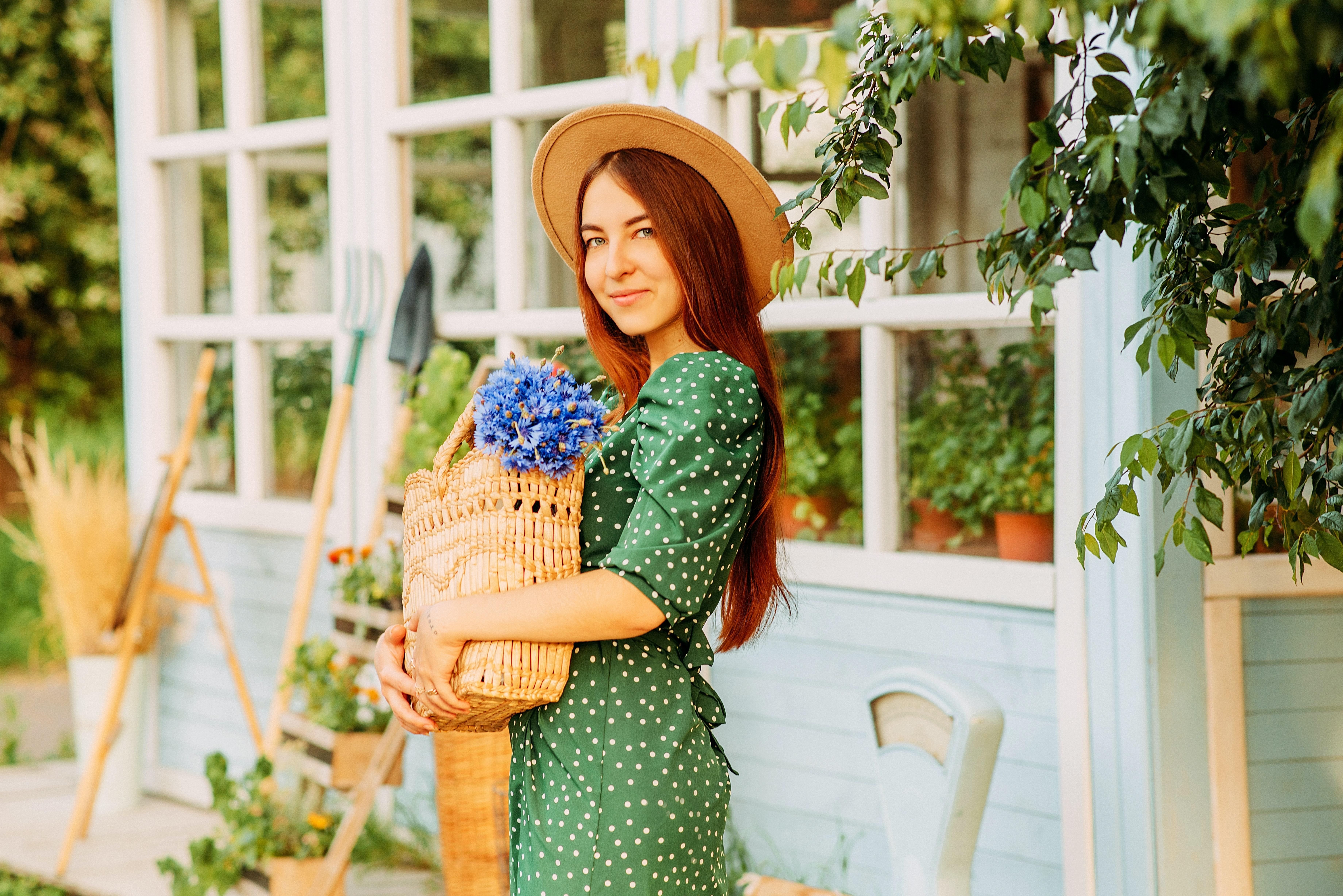 mulher a fazer jardinagem com chapéu e vestido verde com bolas brancas