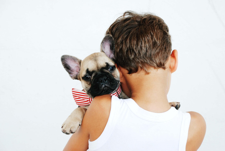 criança a abraçar um cão bebe