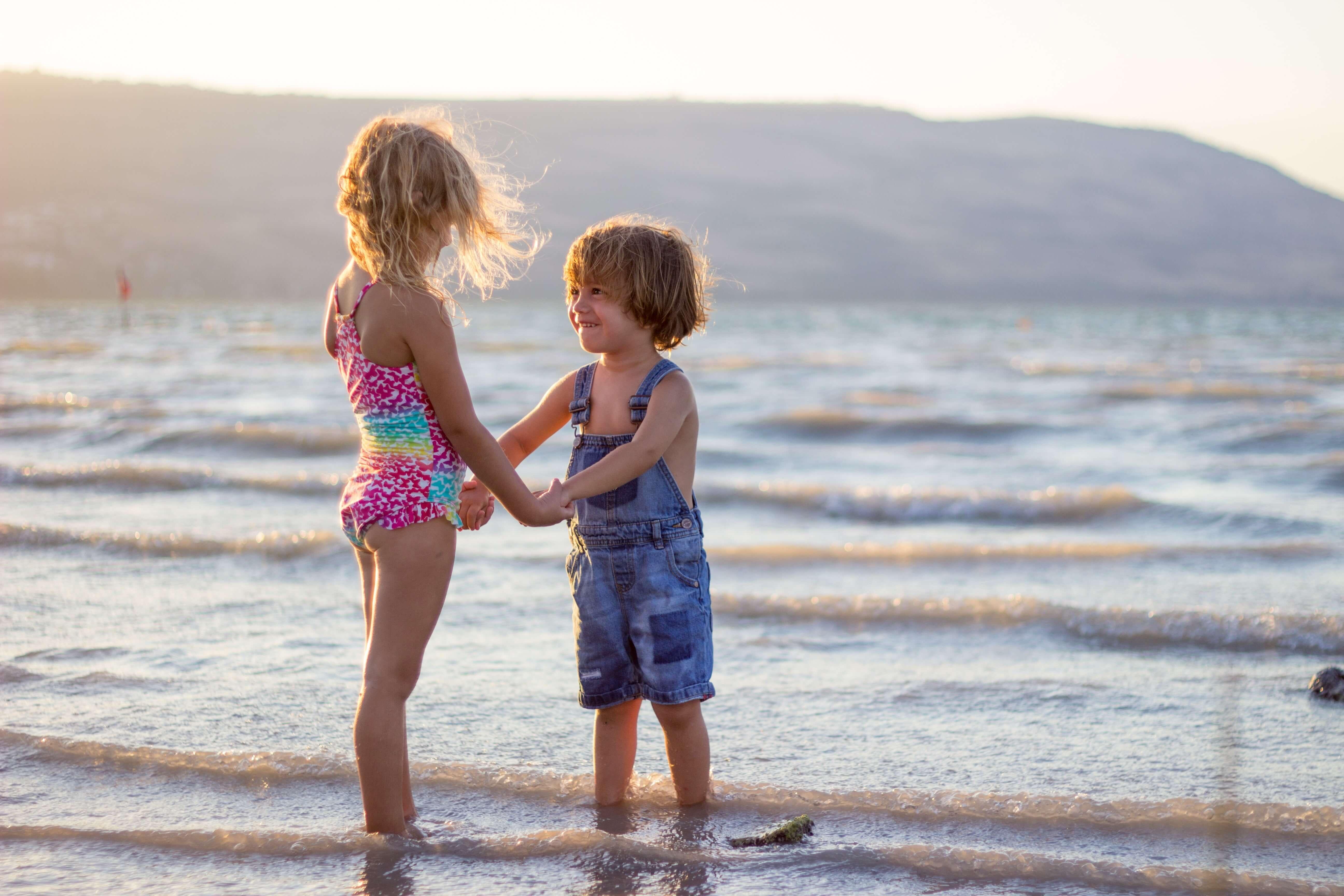 menina e menino de mãos dadas a olhar um para o outro na praia com os pés no mar