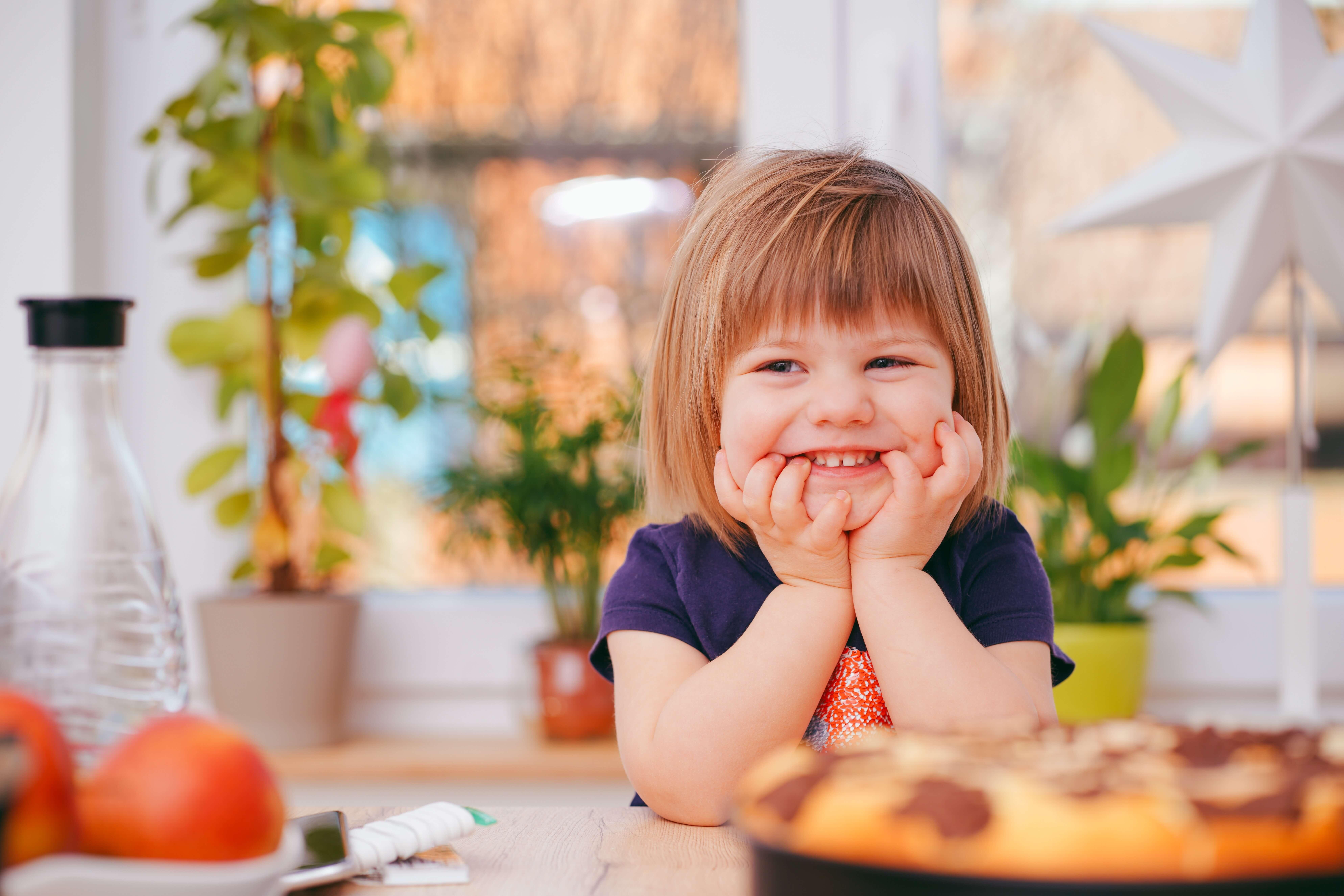 uma criança sorridente com a cara apoiada nas mãos