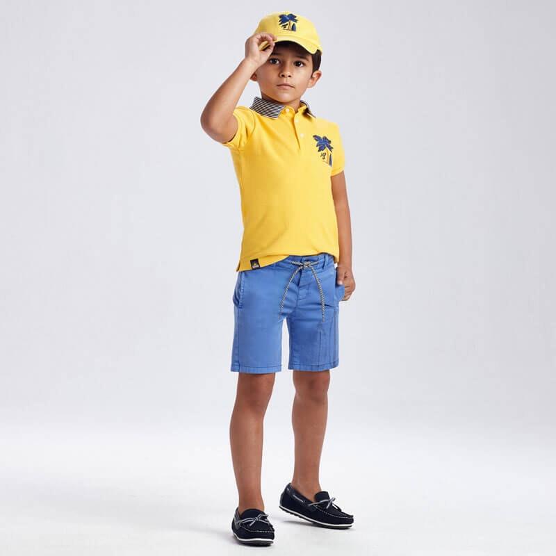 rapaz vestido com sapatos de vela, calções azuis e polo amarelo e chapéu amarelo da mayoral