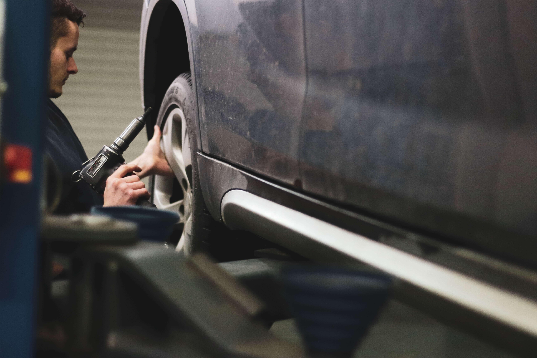 mecánico a mudar a roda de um carro elevado