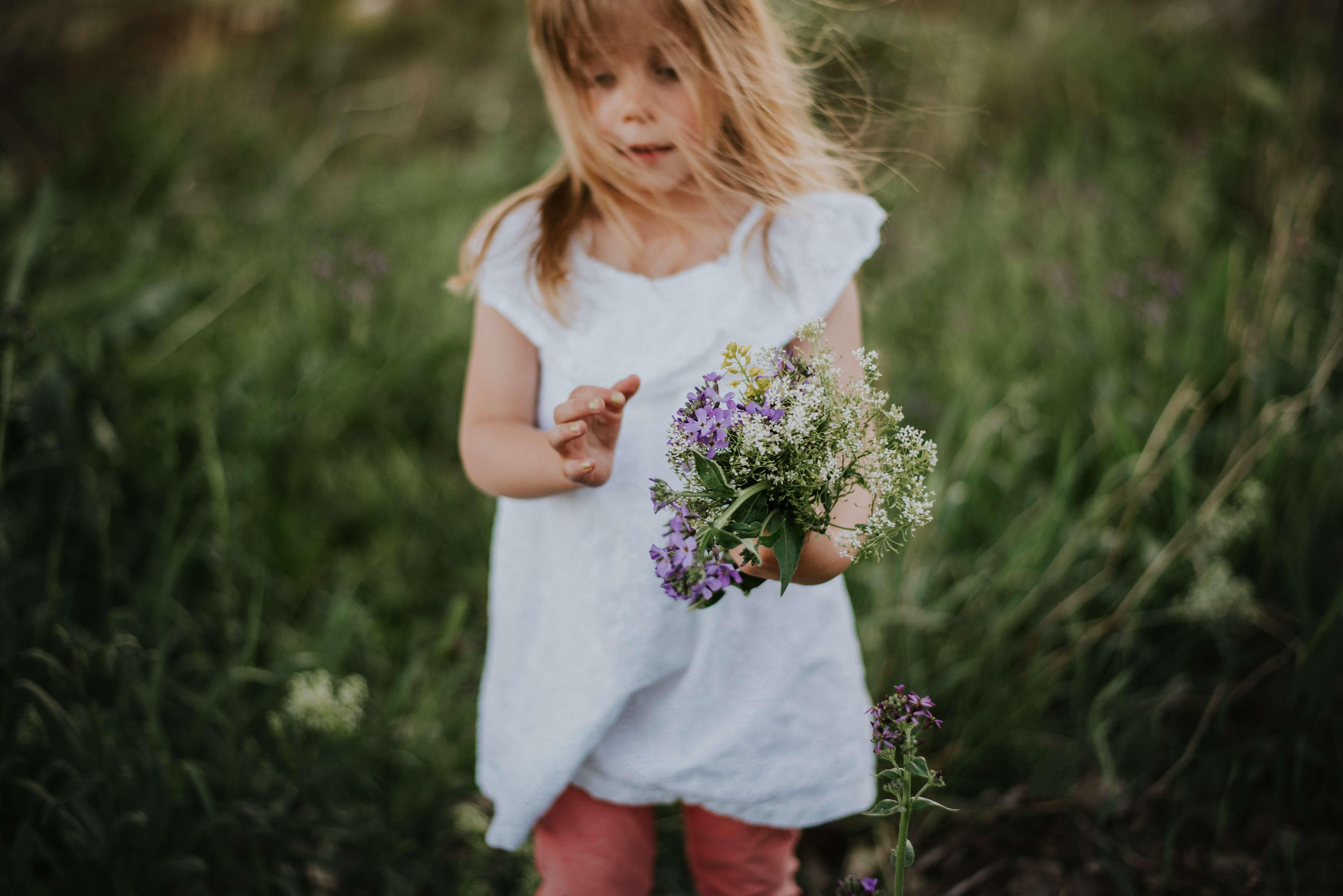 Menina com flores silvestres na mão